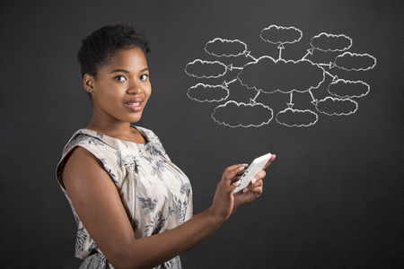 young girl: South African or African American black woman teacher or student holding a tablet with a spider or thought diagram standing against a chalk blackboard background inside