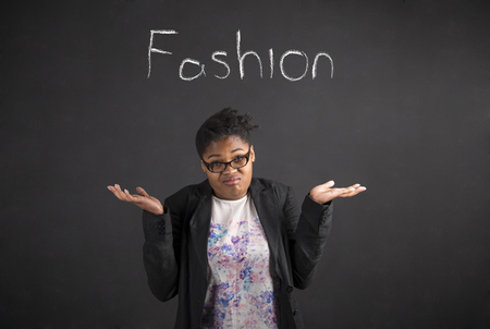 i dont know: South African or African American black woman teacher or student posing with an I dont know about fashion gesture on a chalk blackboard background inside