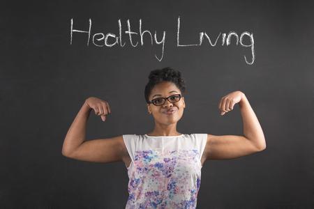 profesor alumno: Sudáfrica o africano profesor americano negro mujer o estudiante con fuertes brazos musculosos vida saludable pie sobre un fondo tiza en el interior Foto de archivo