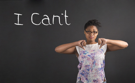 cant: South African or African American black woman teacher or student with thumbs down hand signal I Cant on a chalk black board background inside
