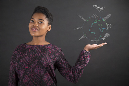 South African or African American black woman teacher or student holding her hand out to the side with a globe for travel standing against a chalk blackboard background inside