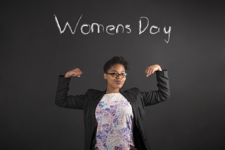 Women's health: South African or African American black woman teacher or student with strong muscular arms for Womens Day standing against a chalk blackboard background inside Stock Photo