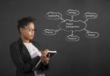 management concept: South African or African American black woman teacher or student writing about project management in a book or diary against a chalk blackboard background inside Stock Photo