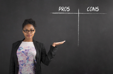 pros: South African or African American black woman teacher or student holding her hand out to the side showing a pros and cons list standing against a chalk blackboard background inside Stock Photo