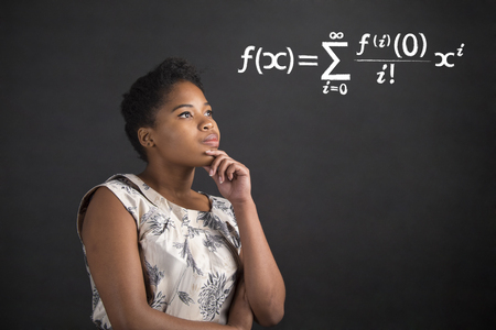 South African or African American black woman teacher or student with her hand on her chin whilst thinking about maths standing against a chalk blackboard background inside Stock Photo