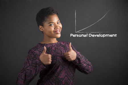 hand signal: South African or African American black woman teacher or student with a thumbs up hand signal to personal development standing against a chalk blackboard background inside Stock Photo