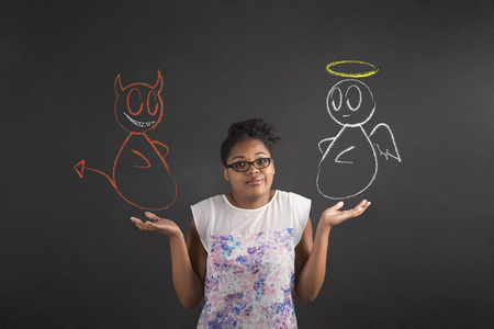 i dont know: South African or African American black woman teacher or student posing with an I dont know angel and devil gesture on a chalk blackboard background inside Stock Photo