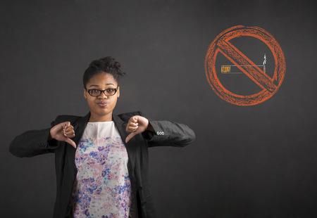 Profesor sudafricano o afroamericano negro mujer o estudiante con los pulgares hacia abajo de señales de mano a no fumar en un fondo negro en el interior de tablero de tiza