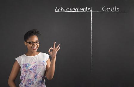 metas: Profesor de la mujer negro sudamericano africano o africano o estudiante de la celebraci�n de una se�al con la mano perfecta con una lista de logros y metas en un fondo de la pizarra de tiza en el interior Foto de archivo