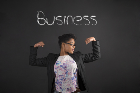 african business: South African or African American black woman teacher or student with strong muscular arms for business standing against a chalk blackboard background inside