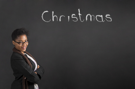 african student: South African or African American woman teacher or student with arms folded thinking about Christmas on chalk black board background