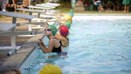 Young girl swims in swimming gala race competition photo