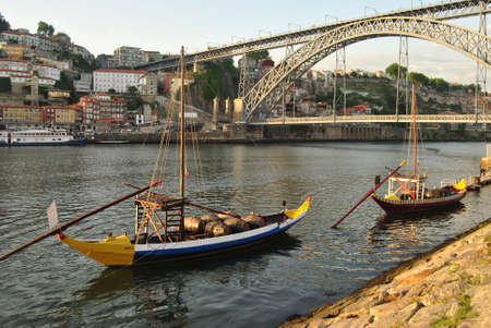 Yellow and blue rabelo boats stopped at dio d'ouro on the quay of Vila Nova de Gaia with the Dom Luís bridge in the background
