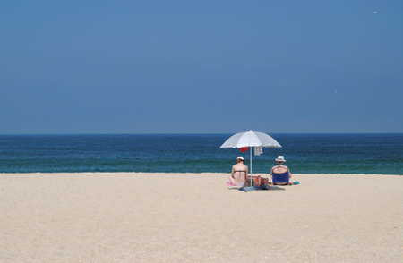Two women sitting on the sand of the beach near the sea with the parasol open enjoying the horizon on the beach