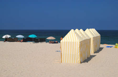 Beach with rental tents with yellow and white striped cloth