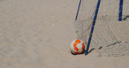 Soccer the sport of the poor - old soccer ball left on the beach next to a goal with broken nets - beach soccer