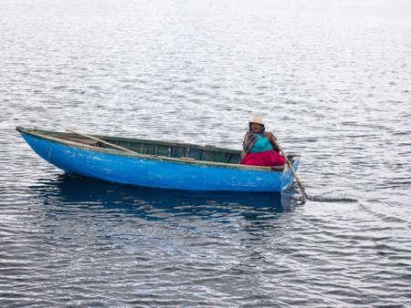 青い船は葦島チチカカ湖にカラフルな女性。