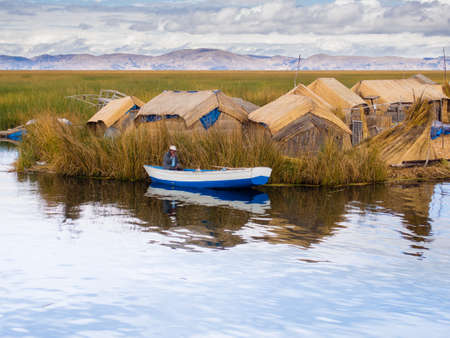 ペルーのチチカカ湖の葦島で小さな青いボートの男