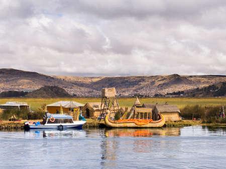 リード島、チチカカ湖のペルーの伝統的・近代的な船を持つ男性。 報道画像
