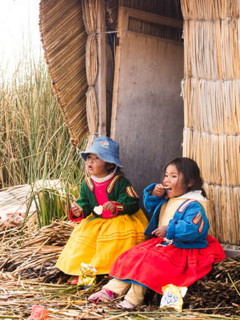 Children in colorful clothing eating in the village in the Reed Islands on Lake Titicaca in Peru.