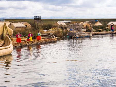 ペルーのチチカカ湖にある葦島の桟橋で子供とカラフルなドレスの女性。 報道画像