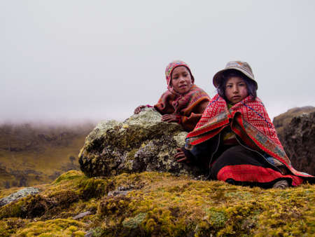 Brother & sister in colorful clothing alone in the Andes mountains of Peru.