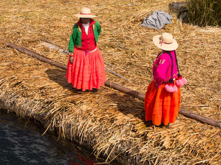 ペルーのチチカカ湖の葦島桟橋にカラフルなドレスの女性。