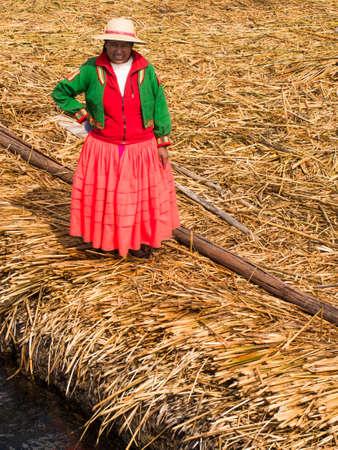 夏にチチカカ湖の葦の島の桟橋に赤いドレスを着た女性。 報道画像