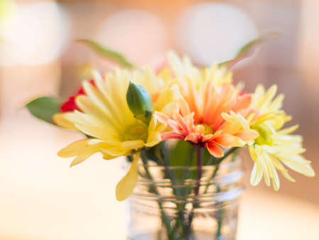 ボケ味を持つテーブルの上の瓶に混合された花束 写真素材
