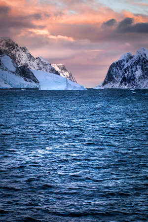 Rugged mountains of Antarctica at sunset or sunrise in pink and orange and cloudy. 写真素材 - 121490910