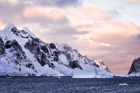 Rugged mountains of Antarctica at sunset or sunrise in pink and orange and cloudy.