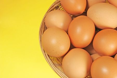Eggs on yellow background Stock Photo