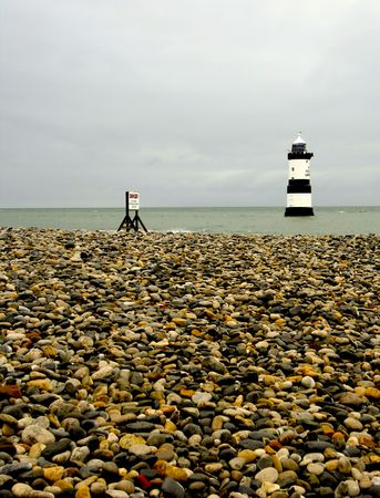 stoney point: stoney beach leading to Trwyn Du Lighthouse at Penmon Point Anglesey Wales UK