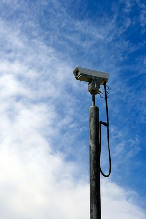 oversee: surveillance camera mounted on a pole to oversee city