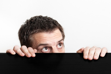 The man looked frightened and he is hiding from something. Stock Photo