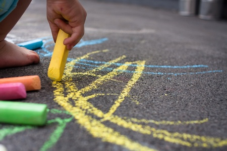 Kid on playground plays with colored chalk Stock Photo