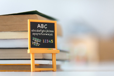 Small blackboard with alphabet in front of books Stock Photo