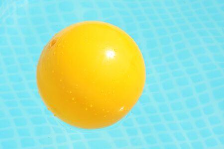 Yellow ball in swimming pool. Looks like a egg yolk.