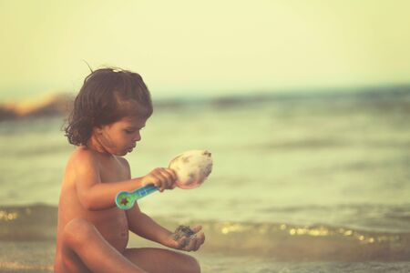 Girl play with shovel in sand on beach. Soft focus.