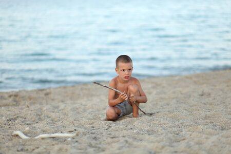 Boy play with stick on beach alone