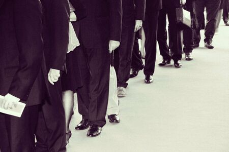 The suits waits in line. Retro black white. Film grain digitally added Stock Photo