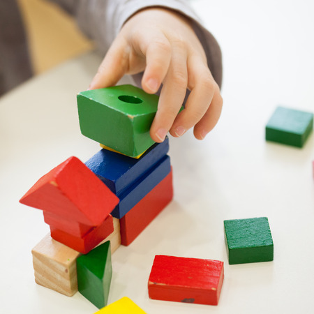 wood blocks: Child play with colored wooden brick shapes on white table. Close up view from above on hands and toys.