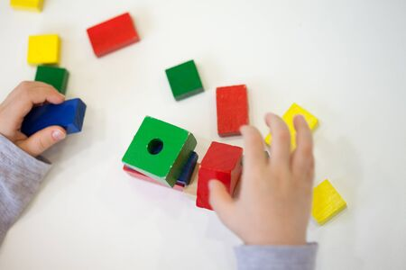 brick: Child play with colored wooden brick shapes on white table. Close up view from above on hands and toys.