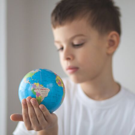 Child holding toy globus in his hand. Day natural window light Stock Photo