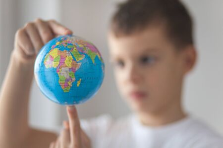 Boy holding toy globus in his hand. Day natural window light. Stock Photo