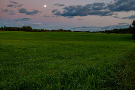 Dramatic landscape of summer sunset, hay field, trees, clouds and moon