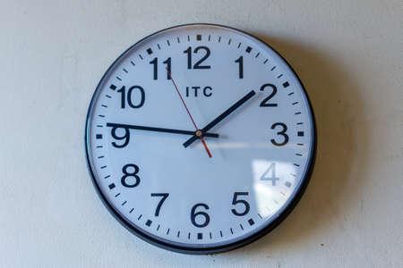 Wall clock with sun glare mounted on a white wall Standard-Bild