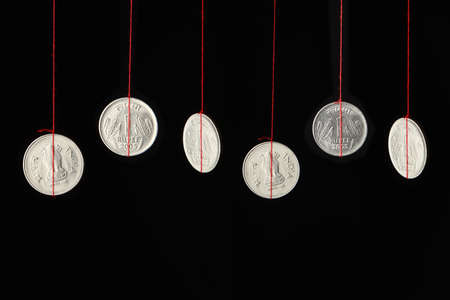 suspend: Conceptual image of Indian coins hanging on strings
