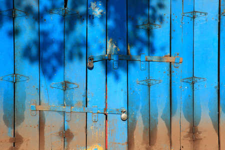 Shadows of leaves falling on an old style blue color wooden folding doors of a closed shop. photo