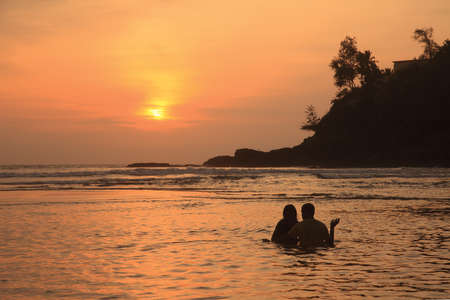 Silhouette of an unidentified couple enjoying in the beach during sunset photo
